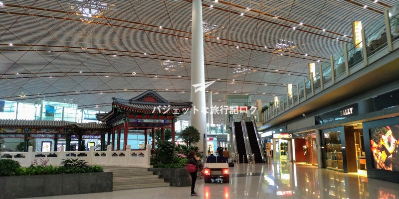 北京首都国際空港の国際線ターミナルの免税店エリア、正面にファーストクラスラウンジがある。