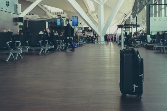 空港をバックにするスーツケース