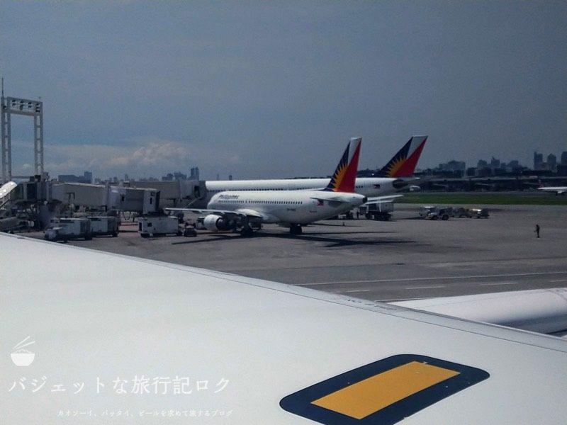ANA搭乗機羽田からマニラ(NH869便) 定刻通りに着陸。フィリピン航空の機体が窓越しに見える